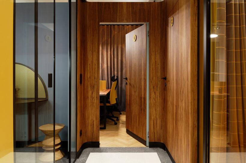 brązowe wnętrze Warszawski Ul od Beza Projekt drewniane drzwi iściany wpołączeniu zprzeszklonymi ścianami