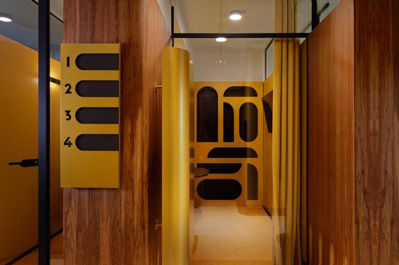 brązowe wnętrze Warszawski Ul od Beza Projekt nowoczesne oznaczenie pokoi wzłotym motywie na drewnianych ścianach