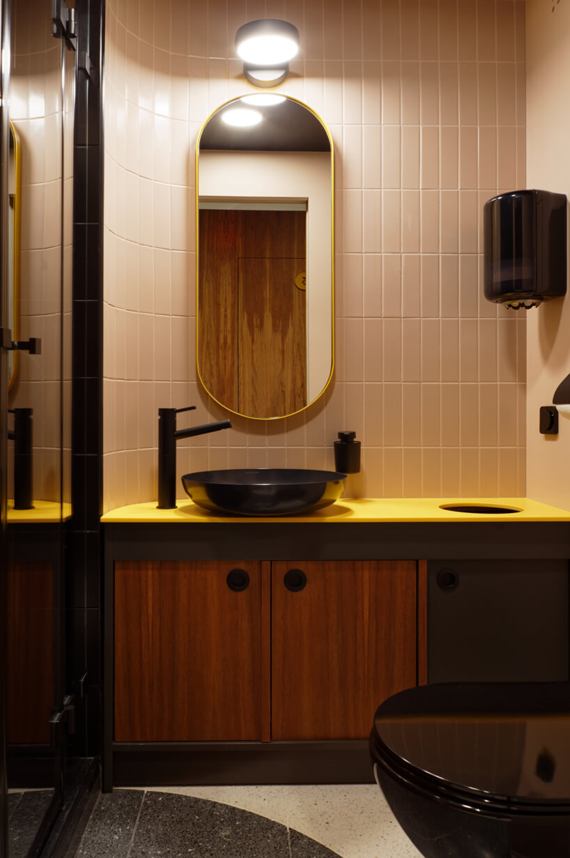 brązowe wnętrze Warszawski Ul od Beza Projekt łazienka zżółtym blatem iczarną armaturą idużym owalnym lustrem