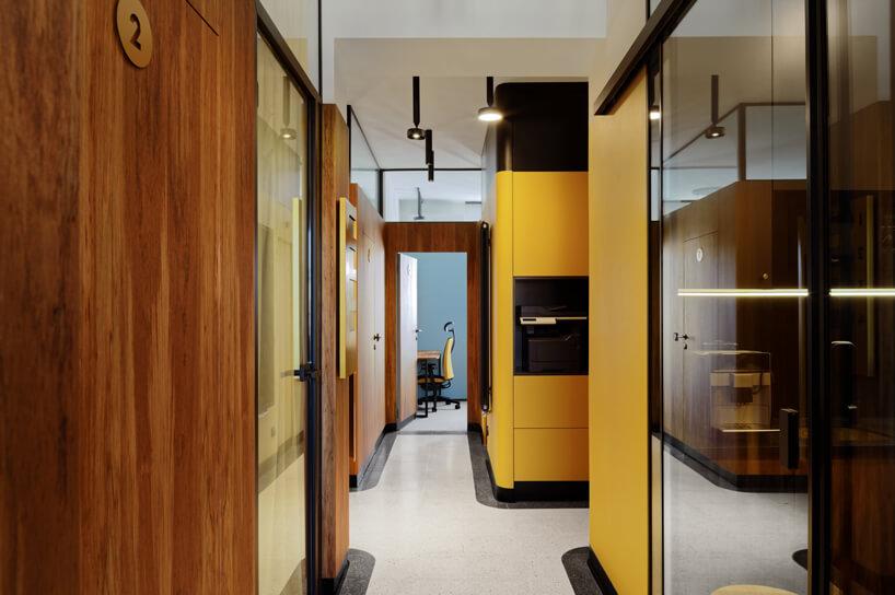 brązowe wnętrze Warszawski Ul od Beza Projekt korytarz wykończony drewnem żółtym plastikiem iszkłem