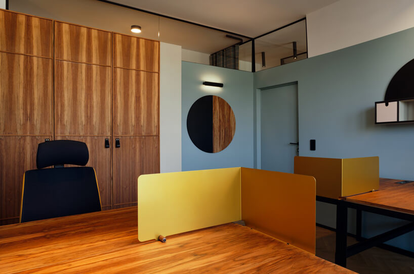 brązowe wnętrze Warszawski Ul od Beza Projekt biuro zniebieskimi ścianami wzestawieniu zdrewnianymi szafami ibiurkami