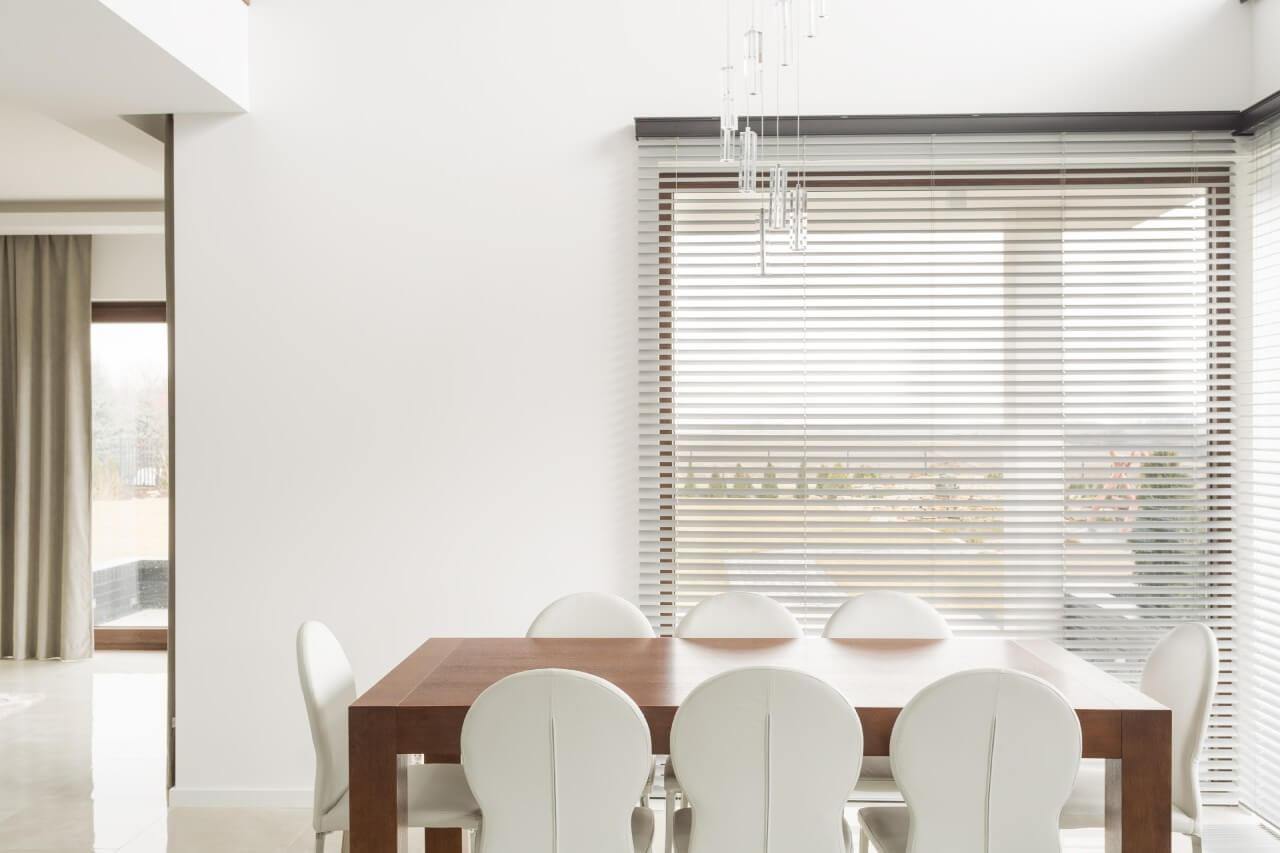 białe żaluzje wtle jadalni zdrewianym stołem ibiałymi krzesłami