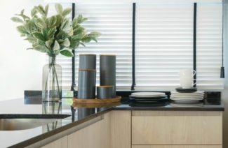 drewiane kuchenne z dodatkami i naczyniami na blacie na tle okna z białymi żaluzjami