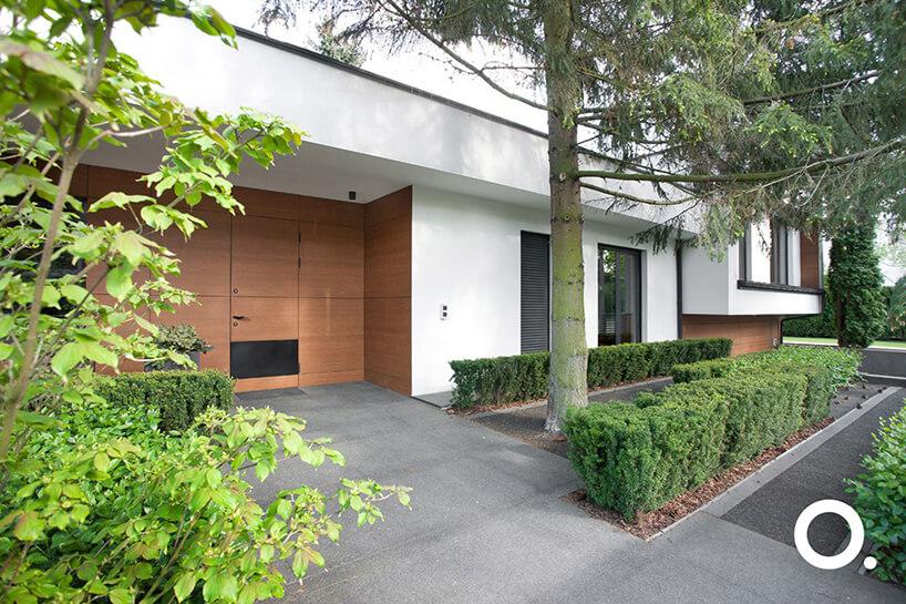 przestrzęń przed białym nowoczesnym domem wzgodzie zbiophilic design od Studio.O.