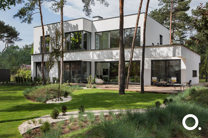 biały dom piętrowy zzogrodem zgodnego zbiophilic design od Studio.O. na tle drzew iglastych