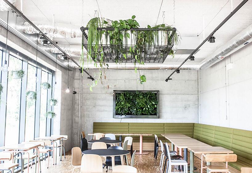 cześc jadalna zmałymi stolikami zkrzesłami wbetonowych ścianach zobrazem zroślin wmetalowej ramie