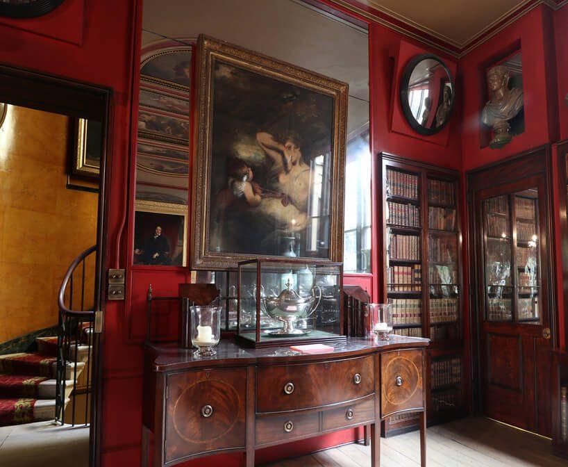 stare wnętrze Domu Architekta projektu Johna Soane'a zdużym lustrem na ścianie za obrazem oraz czerwonymi ścianami