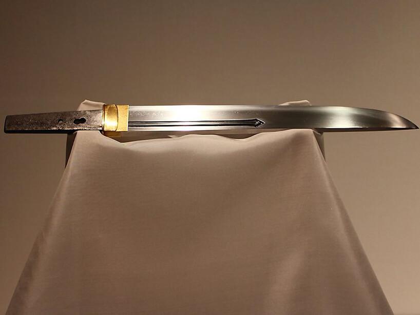 samo ostrze samurajskiego miecza ze złotym wykończeniem na atłasowej podporze