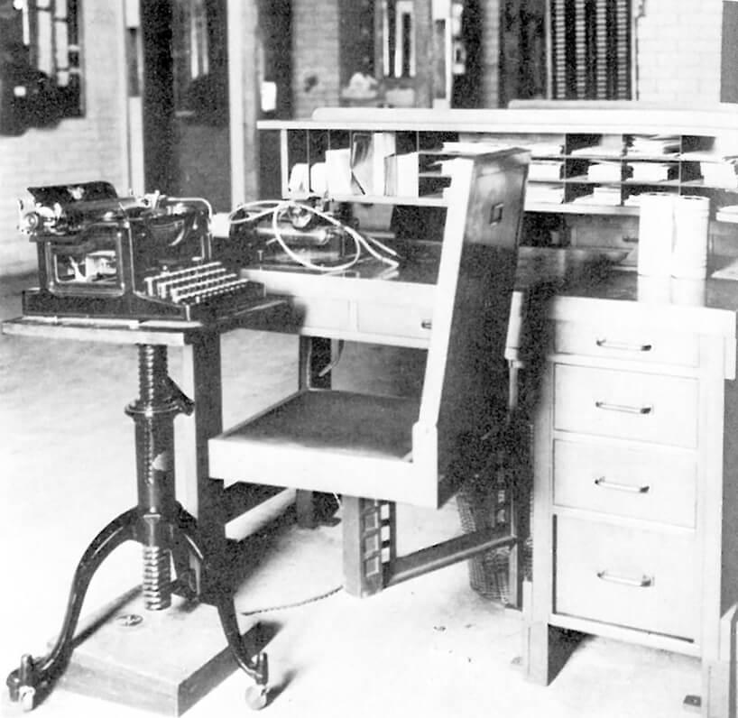 czarno białe zdjęcie stanowisko pracy wLarkin Building małe drewniane biurko zpodwieszonym do niego krzesłem isekretarzykiem na dblatem