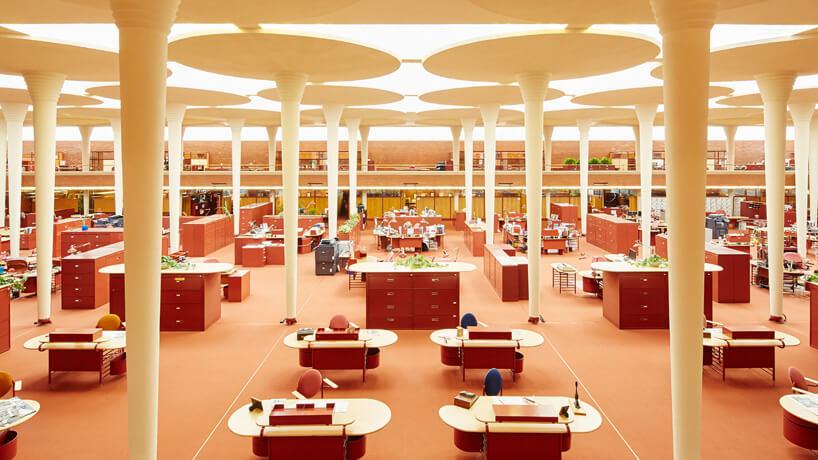 pomarańczowe wnętrze biurowca Johnson Wax Headqarters zowalnymi biurkami sufitem przepuszczającym światło przez zamglone panele zwysokimi filarami