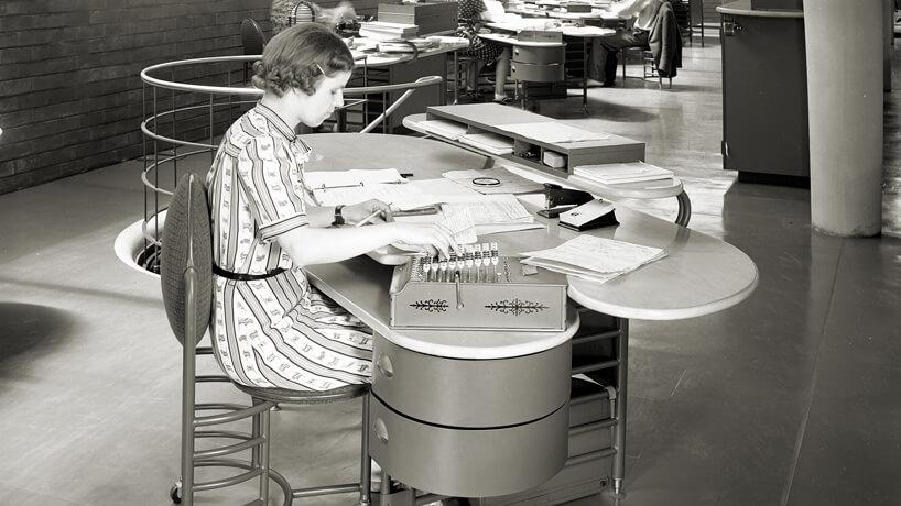 czarno białe zdjęcie pracownicy przy biurku na krześle biurowym zkółkami we wnętrzu biurowca Johnson Wax Headqarters