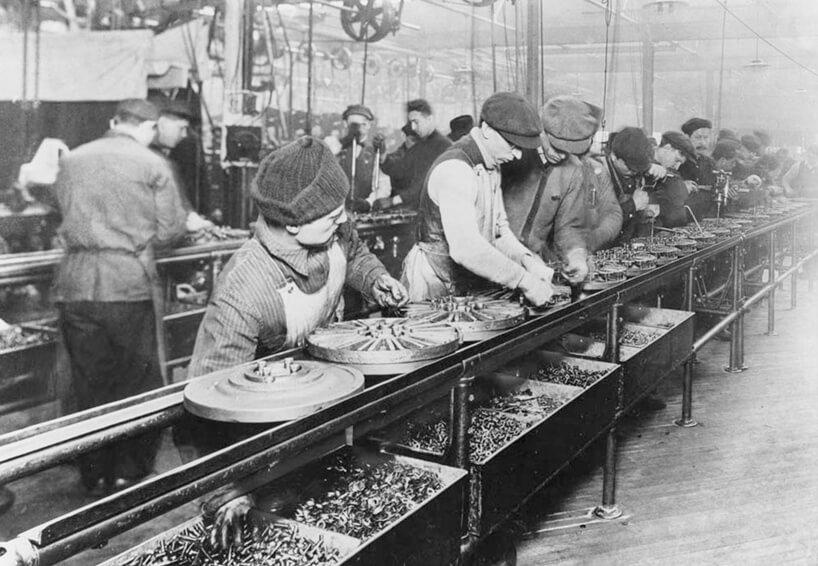 stare czarno białe zdjęcie ludzi przy pracy na taśmie produkcyjnej wfabryce Henry'ego Forda