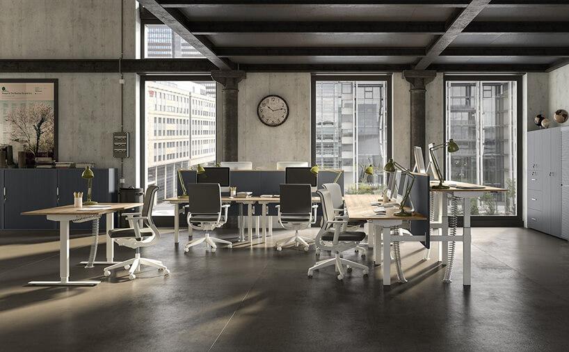 ciemny open space zregulowanymi biurkami zdrewnianym blatem