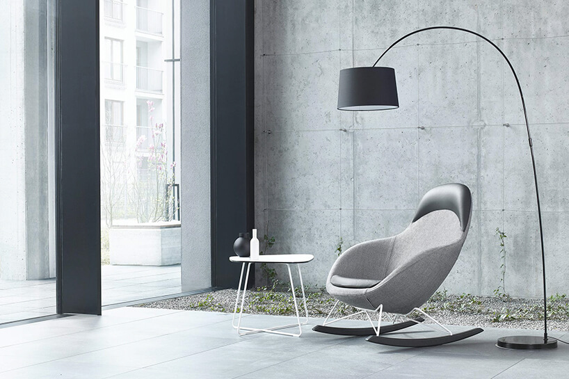 nowoczesna minimalistyczna aranżacja wnętrza zszarym bujanym fotelem iszarą stojąca lampą
