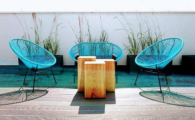 trzy seledynowe fotele zplastikowych pasków na tarasie na tle traw wdoniczkach