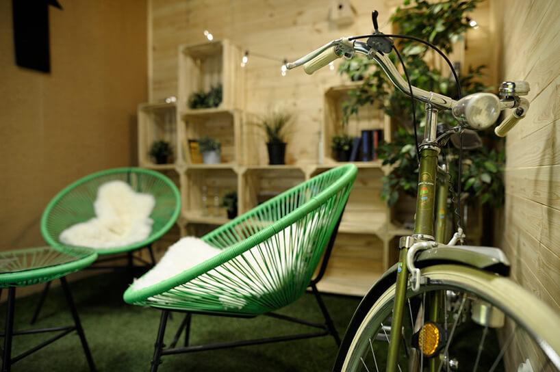 dwa zielone fotele zplastikowych pasków obok starego zielonego roweru wprzestrzeni relaksacyjnej wbiurze