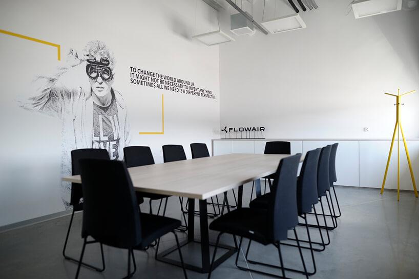 jasna sala konferencyjna zczarnymi krzesłami iróżnymi grafikami na ścianach
