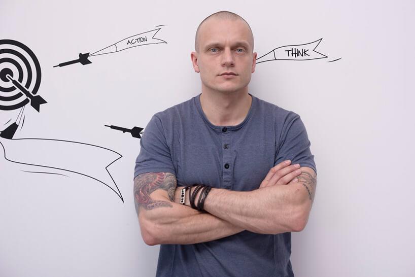 mężczyzna wszarej podkoszulce na tle białej ściany zgrafiką tarczy irzutek