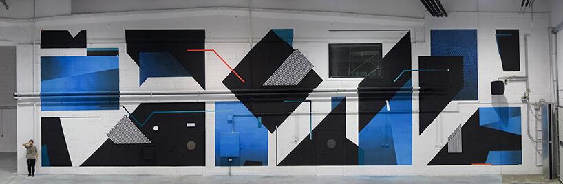 duża biała ściana zczarnymi iniebieskimi grafikami