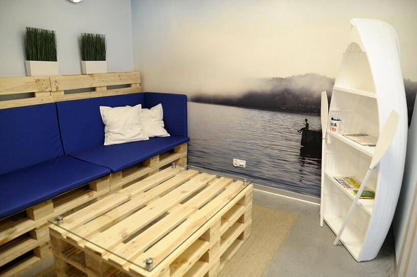 przestrzeń do odpoczynku zsiedziskiem istołem zdrewnianych palet transportowych wszafką wkształcie łódki zwiosłami