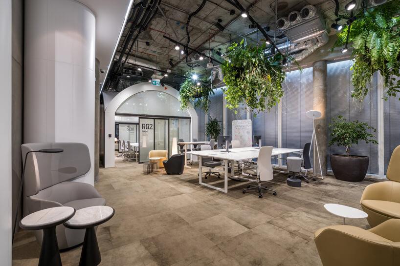 wnętrze biura RBL_ projektu Roberta Majkuta biały zaokrąglony box akustycznyszary fotel zwysokim oparciem przy dwóch małych czarno białych stolikach