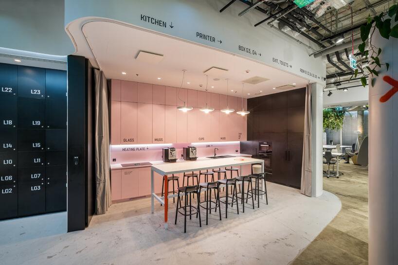 wnętrze biura RBL_ projektu Roberta Majkuta biały zaokrąglony box akustyczny przestrzeń kuchenna zwysokim białym stołem zczarnymi krzesłami zniskim oparciem