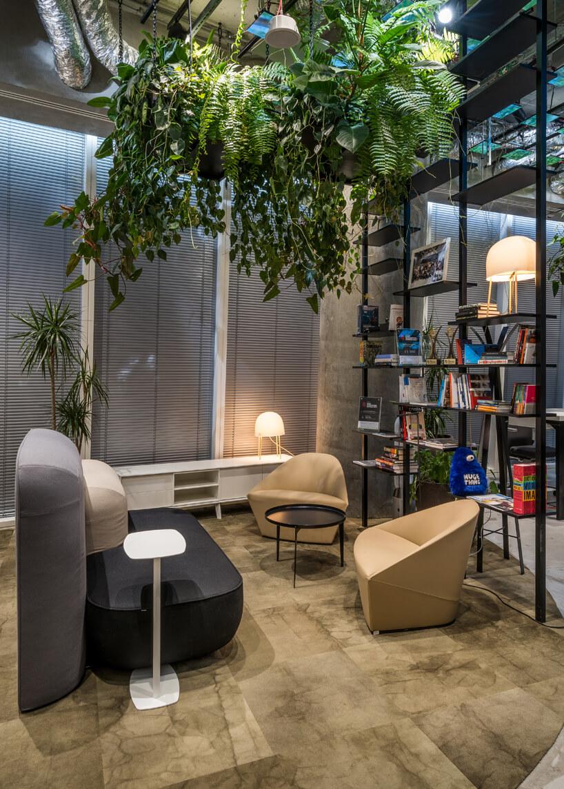 wnętrze biura RBL_ projektu Roberta Majkuta biały zaokrąglony box akustyczny nowoczesne dwa brązowe fotelem przy małym czarnym stolik pod zwisającymi liśćmi zroślin doniczkowych
