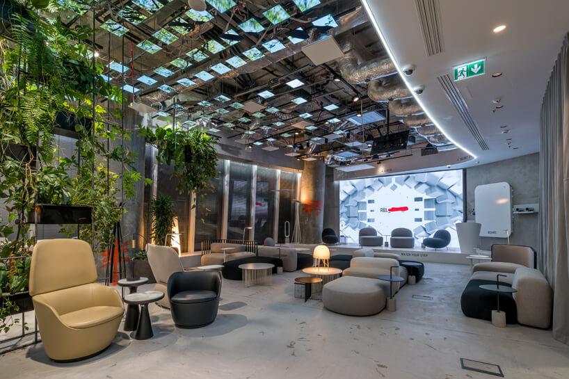 wnętrze biura RBL_ projektu Roberta Majkuta biały zaokrąglony box akustyczny przestrzeń przy recepcji zwieloma niskimi siedziskami na tle dużego ekranu