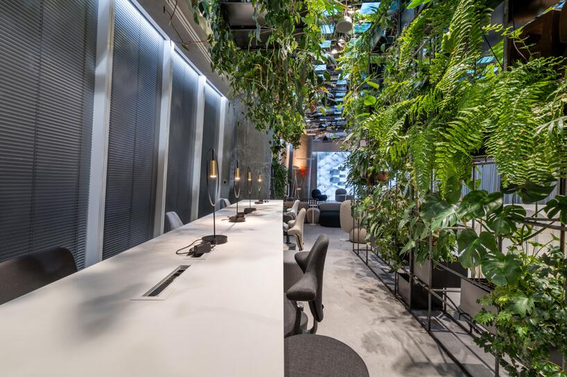 wnętrze biura RBL_ projektu Roberta Majkuta biały zaokrąglony box akustyczny wysokim biały blat zkrzesłami zasłonięty ściana roślin