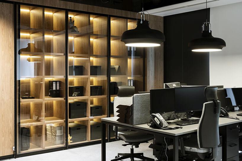 aranżacja biura Stalgast od MADAMA zpołączonymi ciemnymi biurkami iprzeszkloną szafą biurową