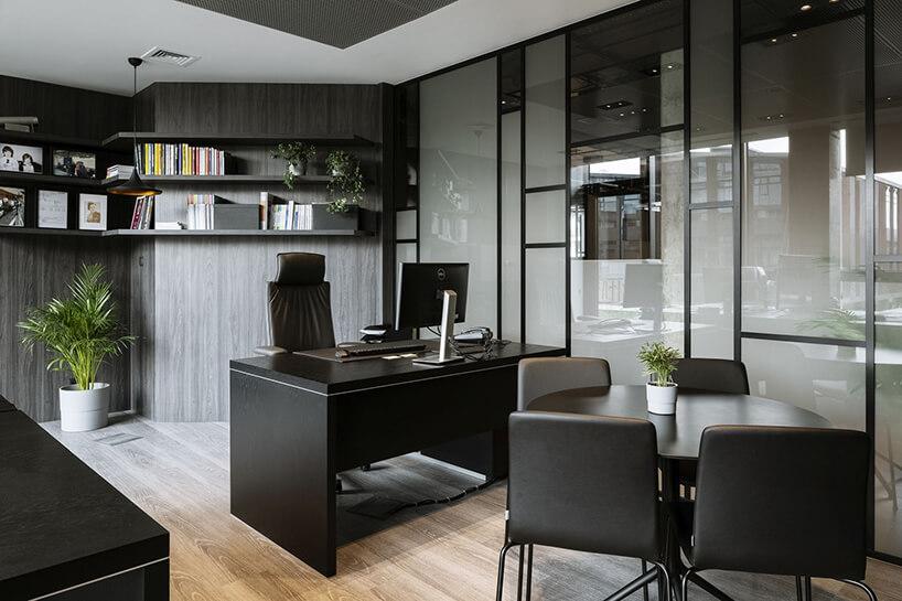 aranżacja biura Stalgast od MADAMA biuro zciemnymi ścianami imeblami na tle przeszklonej ściany