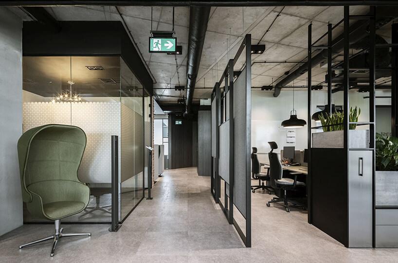 aranżacja biura Stalgast od MADAMA przejście wzaaranżowanej wciemnych kolorach przestrzeni open space