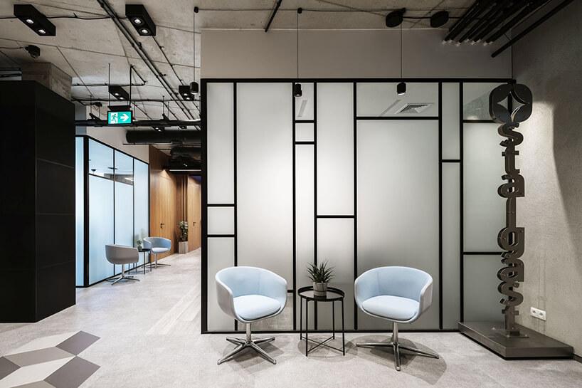 aranżacja biura Stalgast od MADAMA dwa białe fotele przy małym czarnym stoliku na tle szklanej ściany działowej