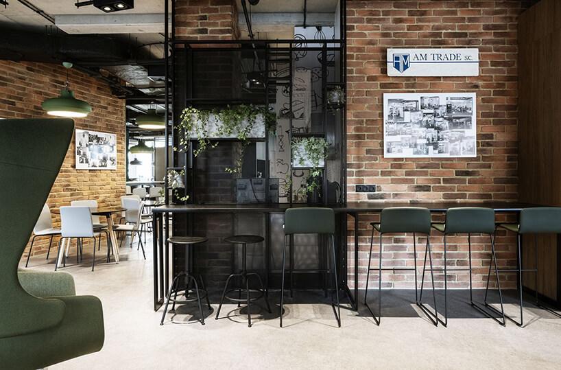 aranżacja biura Stalgast od MADAMA wysoki stół zciemnymi stołkami na tle szklanej iceglanej ściany