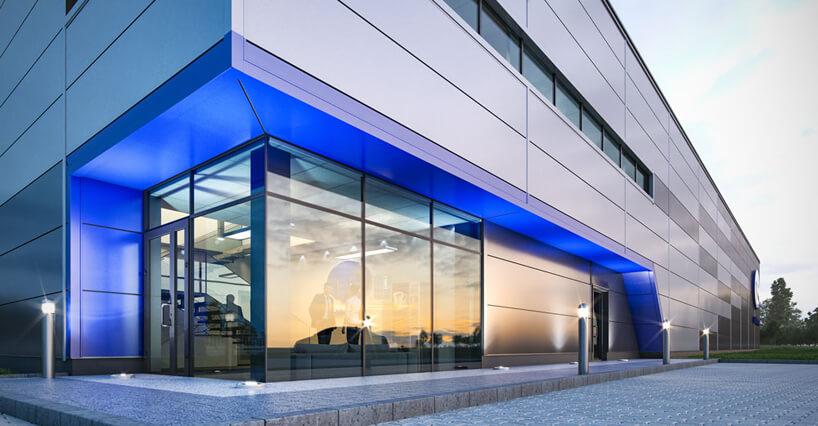 front szarej hali stalowej CoBouw zbiurem zniebieskim podświetlenie