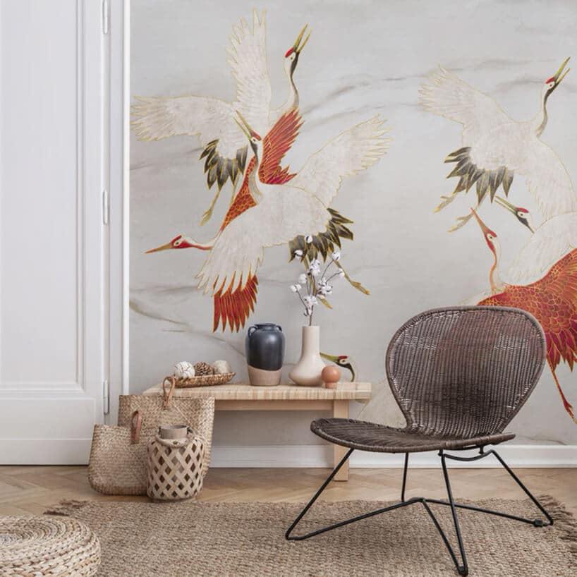 nowoczesne ratanowe krzesło zzszeroko rozstawionymi nogami przy małym stoliczku przy ścianie zczerwonymi ptakami