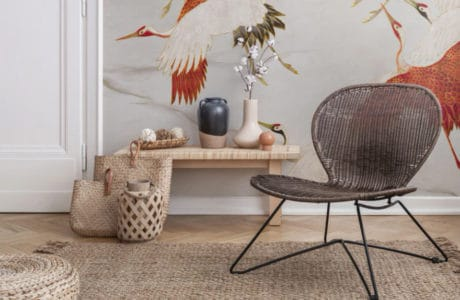 nowoczesne ratanowe krzesło z z szeroko rozstawionymi nogami przy małym stoliczku przy ścianie z czerwonymi ptakami