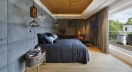 szara sypialnia zdużym łóżkiem imiękką ścianą zzagłowia