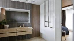 łazienka zpodwieszaną szafką zumywalką wkolorze piasku iwzorze marmuru