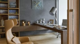 gabinet ze stylowymi skórzanymi fotelami oraz ciemno brązowymi biurkiem idużym oknem zroletą rzymską