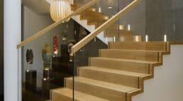 jasno drewniane schody zbarierką szklaną oraz wykończeniem drewnianym