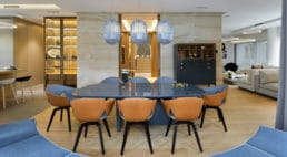 duża jadalnia zpomarańczowo-niebieskimi krzesłami iwiszącymi wazonami