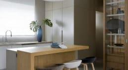 kuchnia zwyspą zdrewnianym blatem itrzema krzesłami wróżnych kolorach