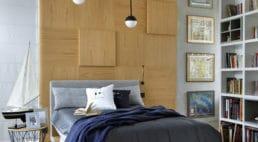 sypialnia zelementem ściany wdrewnie oraz szarościach