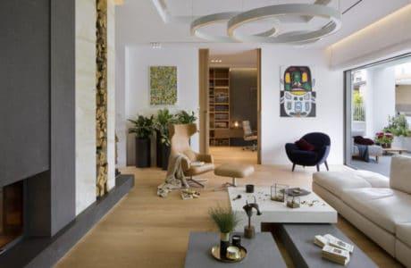 sufit z dwoma świetlnymi ringami wiszącymi nad stołem przy białej skórzanej kanapie