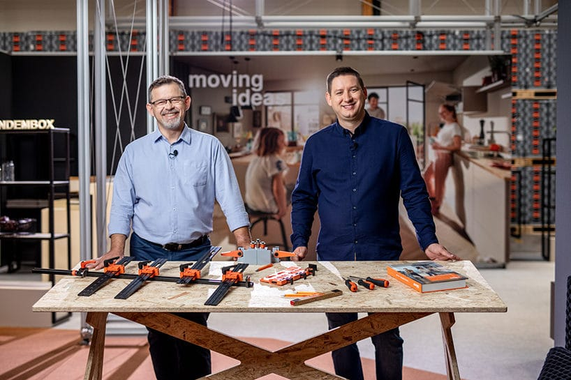 dwóch mężczyzn przy stole ze sklejki zprezentacją produktów Blum