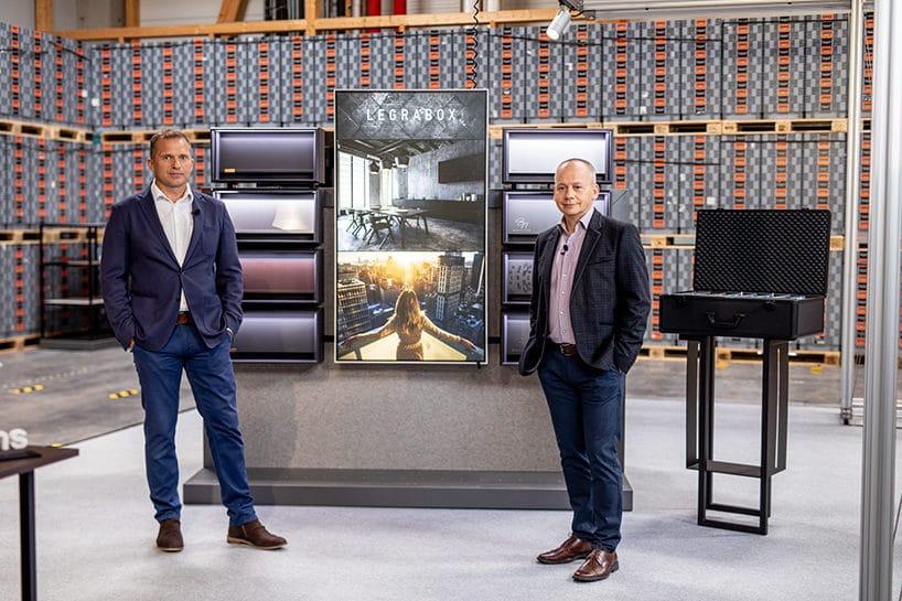 dwóch mężczyzn wgarmiturach przy prezentacji LEGARBOX od Blum