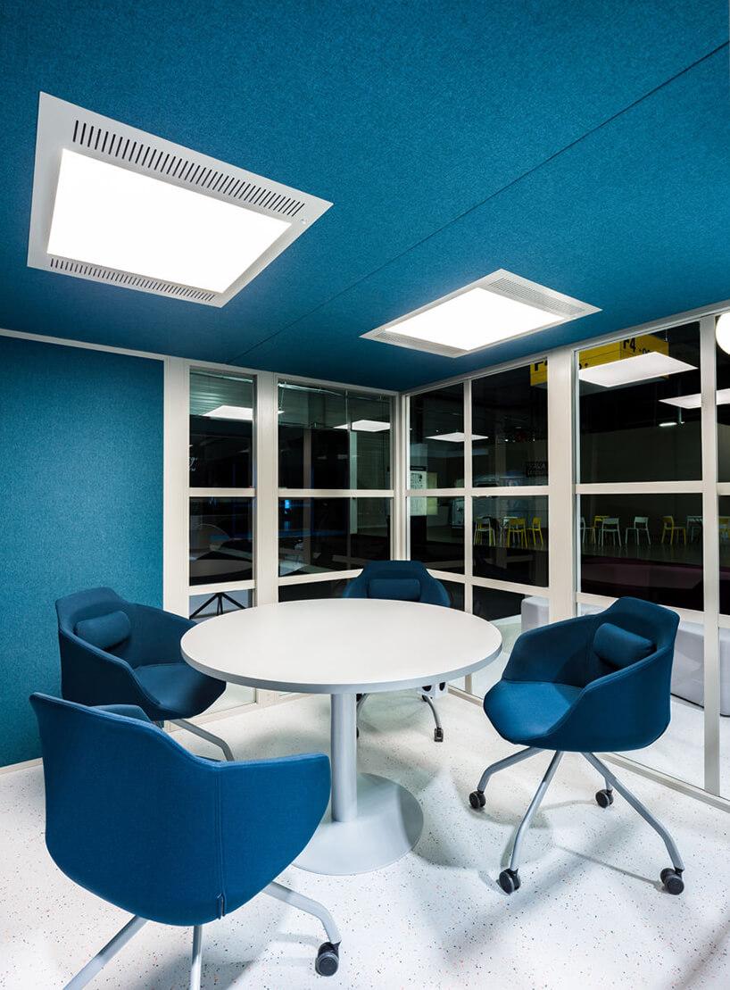 nowoczesny boks akustyczny Hako od MDD duży niebieski boks wewnątrz zniebieskimi krzesłami na kółkach ibiałym stolikiem