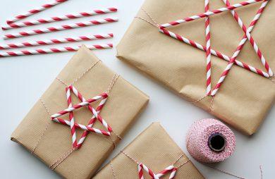 trzy prezenty zapakowane w papier obok biało-czerwonego sznurka