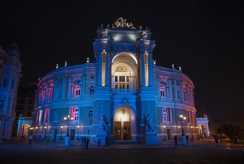 zabytkowy owalny budynek zoświetloną fasadą na niebiesko iczerwono
